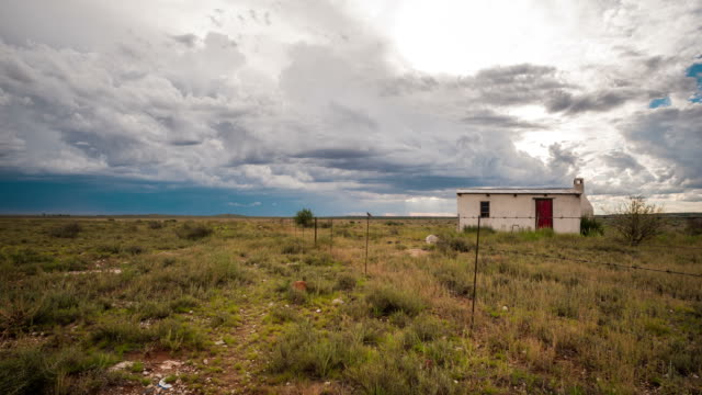 vidéos et rushes de linear vertical timelapse of a typical karoo farm landscape with a small house next to a fence post, scattered clouds in a vast open scene - karoo