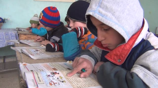 Lined up in a chilly schoolyard in northeast Syria primary school students say good morning to their teachers in the Kurdish language before rushing...