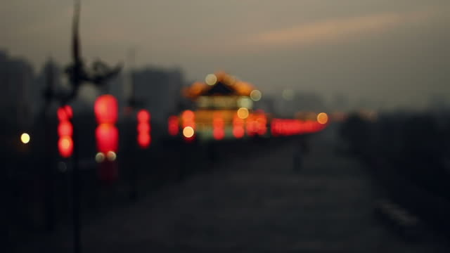 ms r/f lined with lanterns on ancient city wall at sunset/xian,shaanxi,china - dissolvenza in chiusura video stock e b–roll