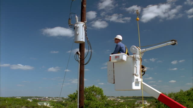 cs slo mo ws ha lineman in bucket truck looking up at power lines / johnson city, texas, usa - maintenance engineer stock videos & royalty-free footage