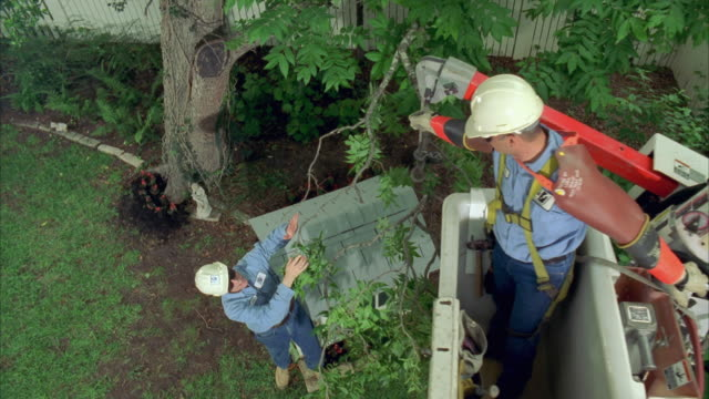 cs slo mo ws lineman in bucket truck lowering branch to lineman standing next to dog house / austin, texas, usa - installing stock videos and b-roll footage