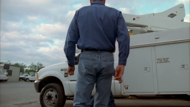 cs slo mo ws lineman walking across company yard and entering truck / johnson city, texas, usa - see other clips from this shoot 1842 stock videos & royalty-free footage