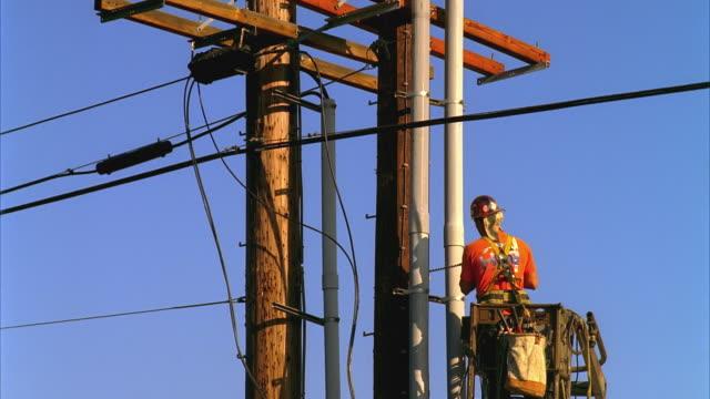ws lineman working on top of electricity pole, california, usa - addetto alla manutenzione video stock e b–roll