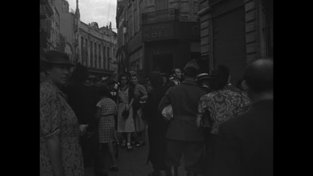 vídeos de stock e filmes b-roll de lines of men walk on city street pan street scenes of a busy french city with man pushing bicycle traffic moving past people standing around / women... - town hall