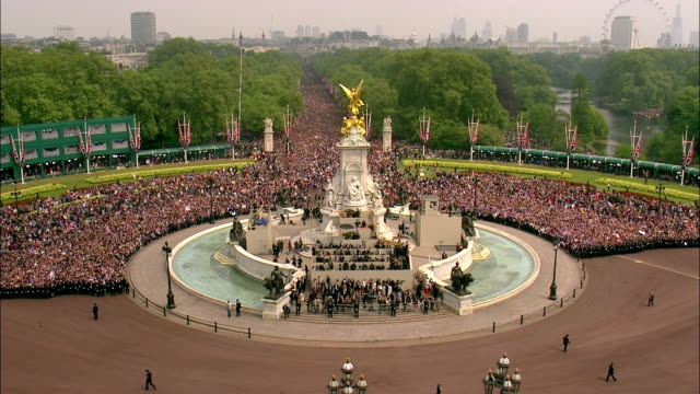 vídeos de stock e filmes b-roll de lines of police officers slowly let the huge crowds on the mall approach the front of buckingham palace during the royal wedding celebrations... - bandeira da grã bretanha
