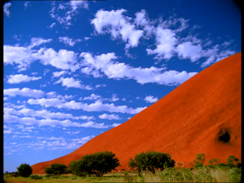 lines of white clouds float above ayers rock in australia. - naturwunder stock-videos und b-roll-filmmaterial