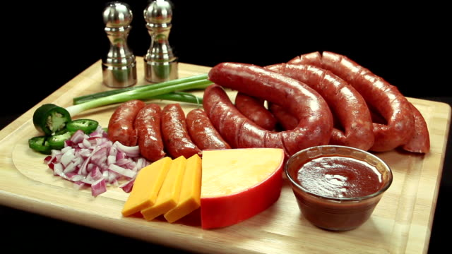link sausage on wood cutting board with aminities. wide shot. - cutting board stock videos and b-roll footage