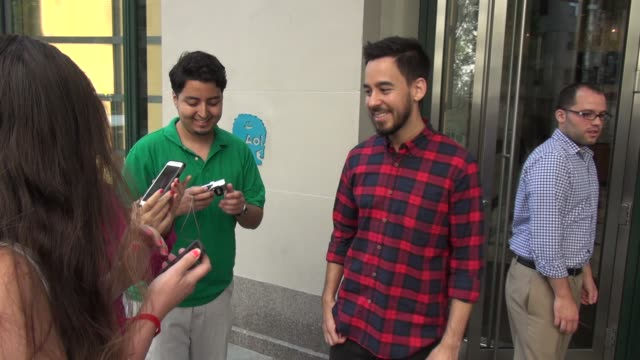 """linkin park's mike shinoda wife anna exit the huffington post and mike poses for photos with fans while anna poses with her book """"learning not to... - linkin park stock videos and b-roll footage"""