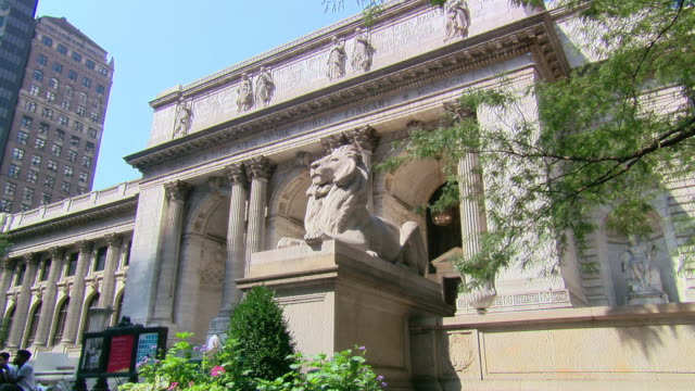 LA Lion statue and entrance of the New York Public Library, with pedestrians / New York, United States