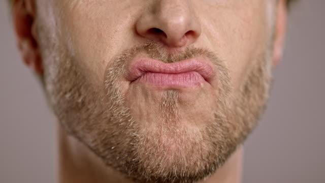 läpparna av en kaukasiska man med skägg som lurar runt - rynka ihop ansiktet bildbanksvideor och videomaterial från bakom kulisserna
