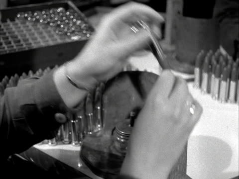 vidéos et rushes de lipsticks are placed into their containers and fired over a small flame at the yardley cosmetics factory. 1955. - rouge à lèvres