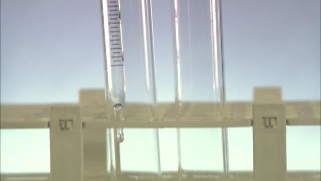 vidéos et rushes de cu, td, liquid being dropped into glass vial in laboratory, london, england - quatre objets