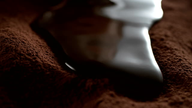 vídeos de stock e filmes b-roll de liquid chocolate flowing on cocoa powder. super slow motion - chocolate