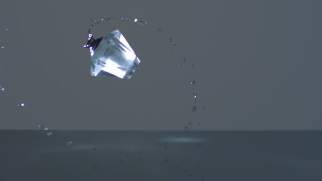 WS SLO MO Liquid contained perfume bottle thrown in mid-air / New York City, New York, USA