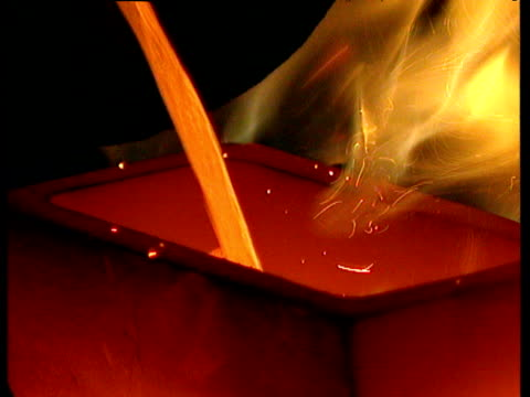 Liquid gold pours out of cylinder into roaring flames of furnace