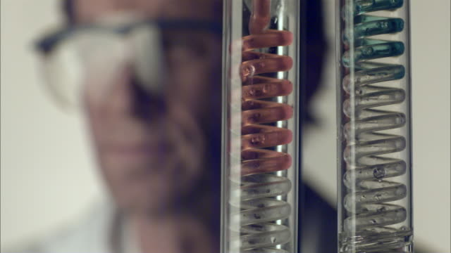 SLO MO CU SELECTIVE FOCUS Liquid in spiral test tubes, lab technician in background / Vienna, Austria
