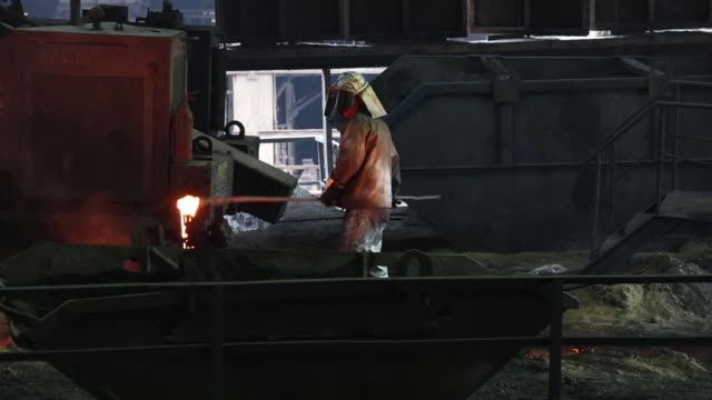 liquid metal flows from the blast furnace at the arcelormittal steel plant in zenica, bosnia, on wednesday, march 16 a worker dressed in heat... - steel stock videos & royalty-free footage