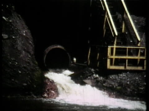 1966 ha liquid pouring out of a drain into the cuyahoga river with a factory on the bank / ohio, united states - fiume cuyahoga video stock e b–roll