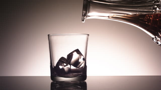cu slo mo liquids and glass / united kingdom - ウォッカ点の映像素材/bロール