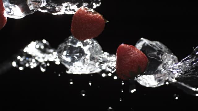 cu slo mo liquids, ice and strawberry / united kingdom - みずみずしい点の映像素材/bロール