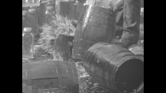 liquor flowing into storm drain on san francisco street / liquor pours out of large bottle / agents smash bottles against the curb, releasing the... - 1920 1929 個影片檔及 b 捲影像