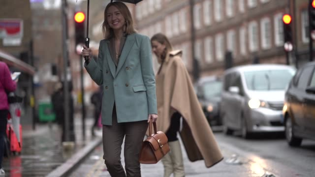 Lisa Aiken wears a blue blazer jacket an orange leather bag brown cropped suit pants shoes earrings an umbrella during London Fashion Week February...