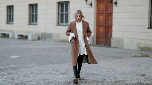 Lisa Hahnbueck is seen wearing white dress with wide sleeves black overknees boots Louis Vuitton Cruise 2018 brown coat Baum und Pferdgarten on...
