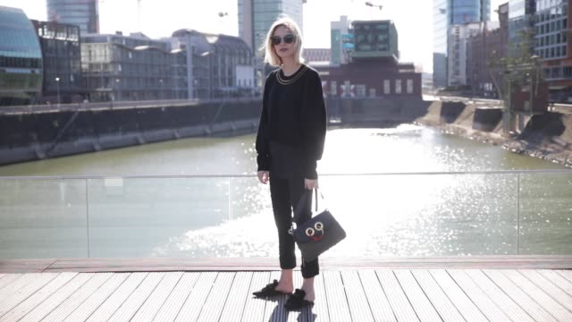 lisa hahnbueck wearing louis vuitton rtw spring/ summer 2017 knit pants mango mules jw anderson pierce bag prada sunglasses on march 30 2017 in... - mule stock videos & royalty-free footage