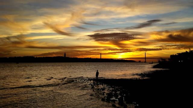 lisbon bridge 25 of april christ and Tajo river with sunset timelapse with people silhouette