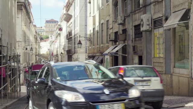 lisbon oldtown street with cars and people - 路面軌道点の映像素材/bロール