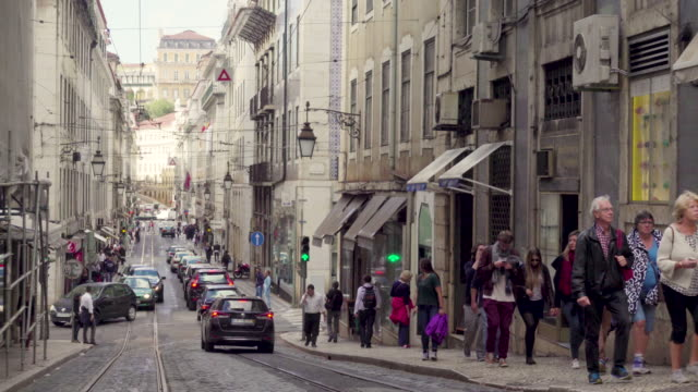 lisbon oldtown street with cars and people - 歩行者点の映像素材/bロール