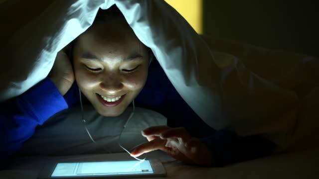 Listening music At Digital Tablet In Under Bed Cover At Night, 4k(UHD)