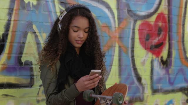 vídeos de stock, filmes e b-roll de ouvir música e mensagens de texto - andar de skate