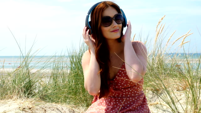 Listening to music, headphones by the sea.