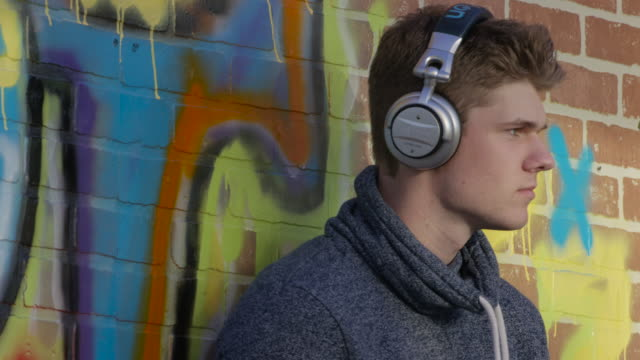 listening to music in an urban city - nodding head to music stock videos and b-roll footage