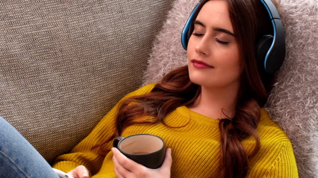 listening to music on headphones relaxing with coffee on sofa. - serene people stock videos & royalty-free footage