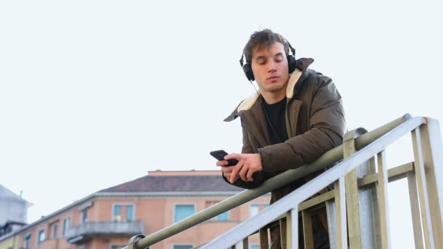 vídeos y material grabado en eventos de stock de listening to music on smart phone - abrigo de invierno