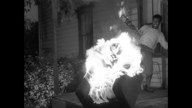 vídeos de stock, filmes e b-roll de 1968 listening to the radio, a man frantically makes fire before dousing a chair with lighter fluid and taking it outside - rodeando