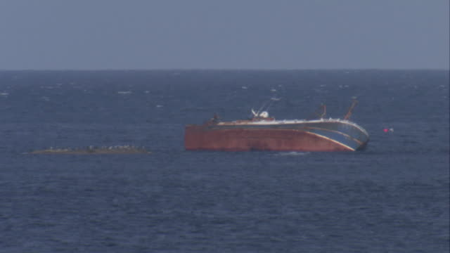 a listing fishing boat sits in the ocean. available in hd. - クロヴィー点の映像素材/bロール