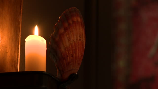 a lit candle illuminates a wall sconce.  - candlelight stock videos & royalty-free footage