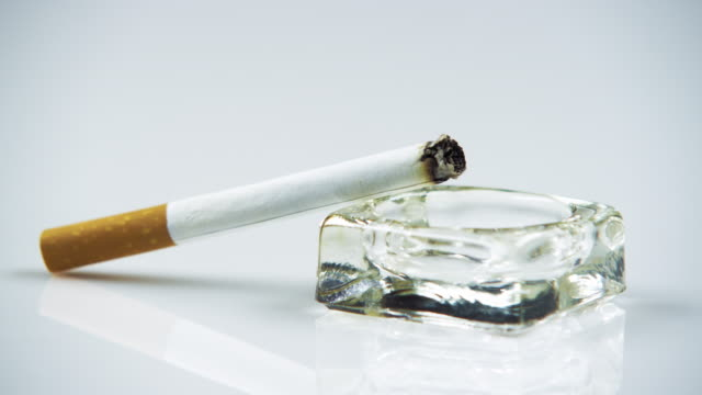 Lit cigarette in an ashtray close up.
