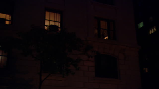 ms lit first-floor window and front entrance of low-rise apartment building, lights shining at night, with traffic / new york city, new york, united states - townhouse stock videos & royalty-free footage