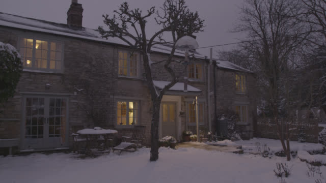 Lit up snowy cottage at Christmas, Oxfordshire, England