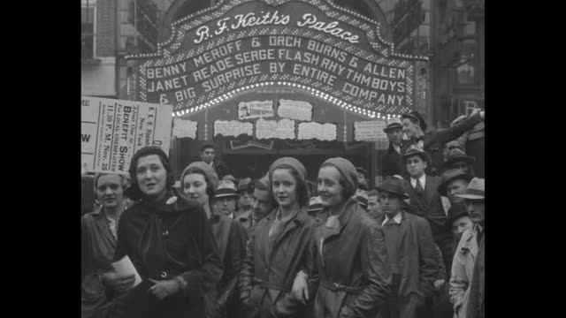 lita grey stands at left with four women wearing berets next to her under the flashing lights of the palace theater marquee and she speaks with a... - basco video stock e b–roll
