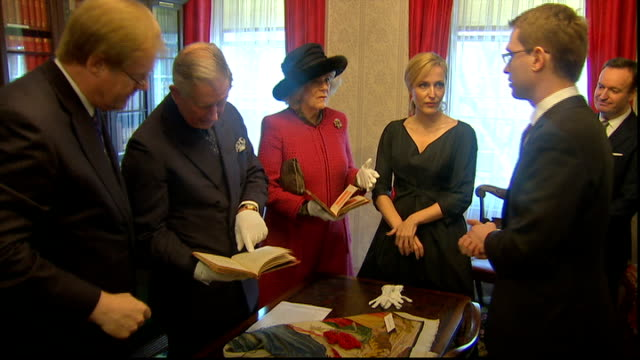 charles dickens bicentenary celebrations; int prince charles turning pages of early copy of dickens' novel charles looking at book as camilla,... - literature stock-videos und b-roll-filmmaterial