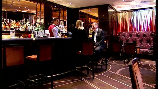 vídeos y material grabado en eventos de stock de new james bond novel launch william boyd and reporter discussing operding a martini sot spirits on shelf behind bar bar worker shaking martini - william boyd