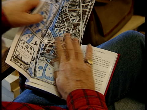 Philip Pullman's latest children's book Oxford Pullman opening out map of Oxford in front of hardback copy of 'Lyra's Oxford' Locations on map...