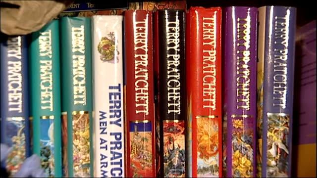 Sir Terry Pratchett dies aged 66 LIB Wiltshire Broadchalke INT GVs Terry Pratchett books on shelf Pratchett typing on computer keyboard as seated at...