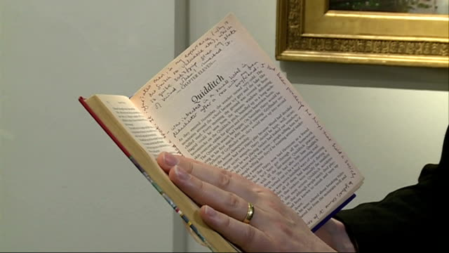 vidéos et rushes de sotheby's book auction preview; man leafing through edition of 'harry potter and the philosopher's stone' book / man taking book out of cabinet /... - harry potter titre d'œuvre