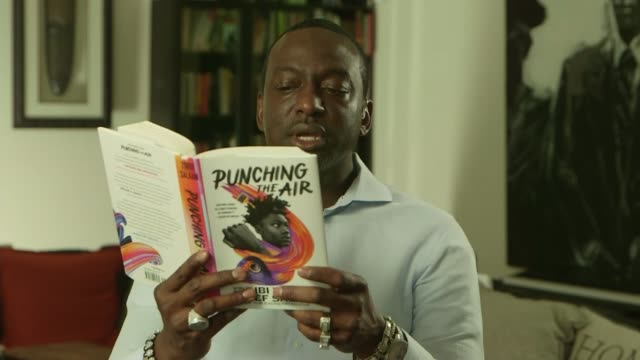 stockvideo's en b-roll-footage met yusef salaam interview; location unknown: int yusef salaam reading from book sot. - literature